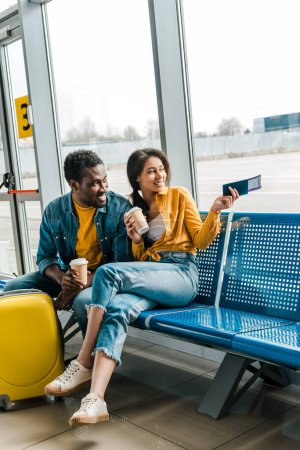 Photo for Smiling african american couple sitting in departure lounge with coffee to go and air tickets and looking at window - Royalty Free Image