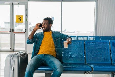 Photo pour Souriant homme d'afro-américain s'asseyant dans le salon de départ avec le café pour aller et parler sur le smartphone - image libre de droit