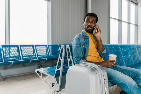 Photo for African american man sitting in departure lounge with coffee to go and luggage while talking on smartphone - Royalty Free Image