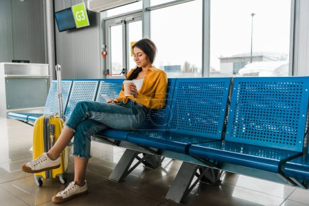 Photo for Smiling african american woman sitting in departure lounge with suitcase, coffee to go and using smartphone - Royalty Free Image