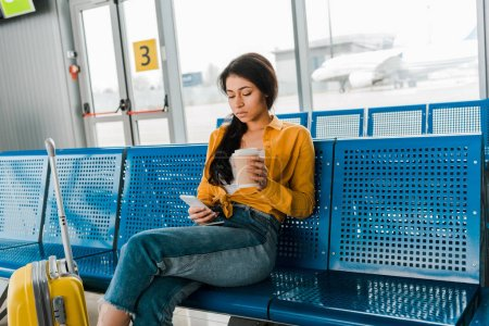 Photo for Sad african american woman sitting in departure lounge with suitcase, coffee to go and using smartphone - Royalty Free Image
