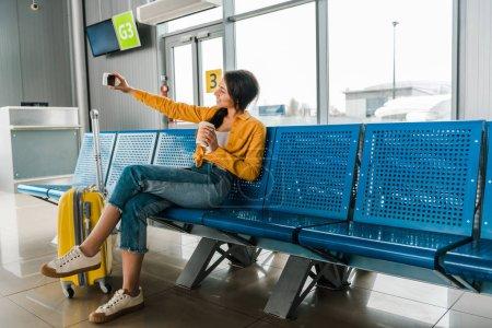 Photo pour Femme afro-américaine souriante assise dans le salon de départ avec valise, café à emporter et selfie sur smartphone - image libre de droit