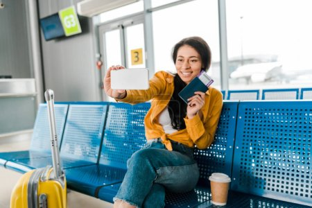 Foto de Happy african american woman sitting in departure lounge with suitcase, coffee to go and taking selfie with passport and air ticket on smartphone - Imagen libre de derechos