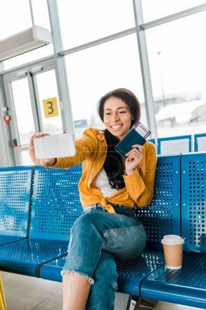 Photo pour Femme afro-américaine heureuse s'asseyant dans le salon de départ et prenant le selfie avec le passeport et le billet d'avion sur le smartphone - image libre de droit