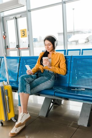 Foto de Happy african american woman sitting in departure lounge with coffee to go and suitcase while listening music in headphones and using smartphone - Imagen libre de derechos