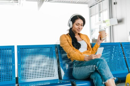 Foto de Happy african american woman sitting in departure lounge with coffee to go while listening music in headphones and using smartphone - Imagen libre de derechos