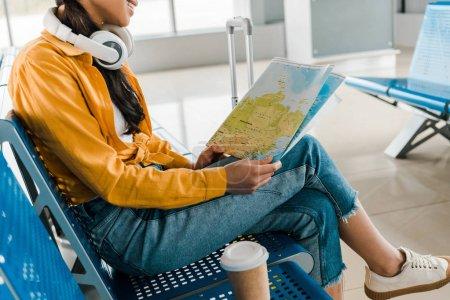 Photo pour Vue recadrée de sourire femme d'afro-américain s'asseyant dans le casque avec le café pour aller et carte dans le salon de départ à l'aéroport - image libre de droit
