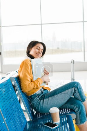 Photo for Smiling african american woman sitting with coffee to go and closed eyes while holding map in departure lounge in airport - Royalty Free Image