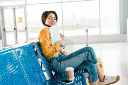 Photo for Pleased african american woman sitting with coffee to go and closed eyes while holding map in departure lounge in airport - Royalty Free Image