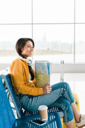 Foto de Smiling african american woman sitting with coffee to go and smartphone on seats while holding map in departure lounge in airport - Imagen libre de derechos