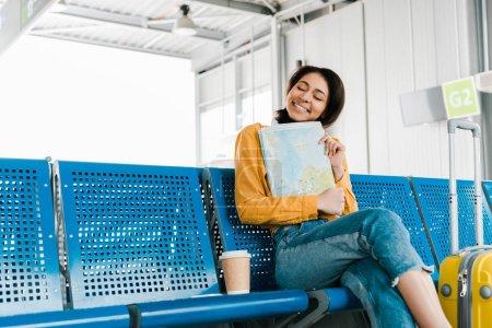 Photo pour Femme afro-américaine souriante s'asseyant avec le café pour aller et carte dans le salon de départ à l'aéroport - image libre de droit