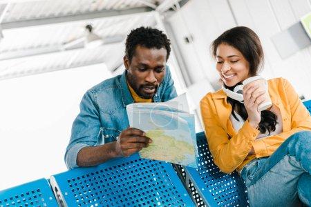Photo pour Femme afro-américaine souriante avec le café pour aller et des écouteurs regardant la carte de fixation de copain dans le salon de départ à l'aéroport - image libre de droit