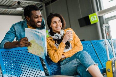 Photo pour Souriant couple afro-américain assis avec la carte dans le salon de départ à l'aéroport et regardant loin - image libre de droit