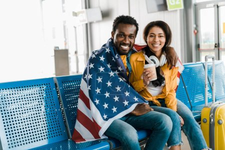 Photo for Smiling african american couple sitting with american flag in departure lounge in airport - Royalty Free Image