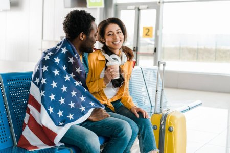 Photo for Happy african american couple sitting with american flag in departure lounge in airport - Royalty Free Image