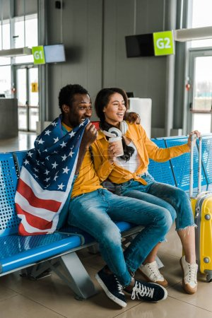 Photo for Happy african american couple sitting with american flag and luggage in departure lounge in airport - Royalty Free Image
