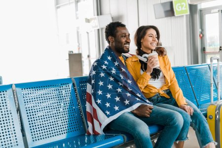 Photo for Happy african american couple sitting with american flag and coffee to go in departure lounge in airport - Royalty Free Image