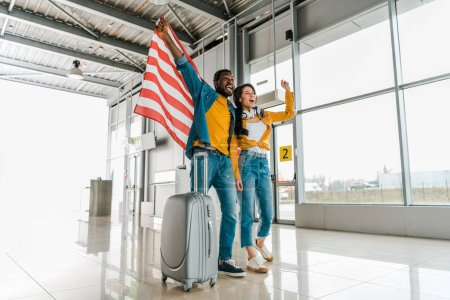 Photo for Happy excited african american couple with american flag and suitcase walking  in departure lounge in airport - Royalty Free Image