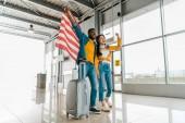 """Постер, картина, фотообои """"Счастливый возбужденный афро-американец пара с американским флагом и чемодан ходить в зале вылета в аэропорту"""""""