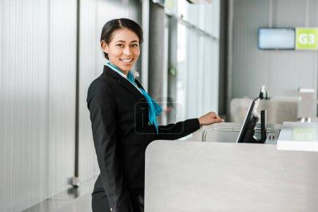 Photo pour Le personnel souriant de l'aéroport afro-américain en uniforme debout au comptoir d'enregistrement et regardant la caméra - image libre de droit