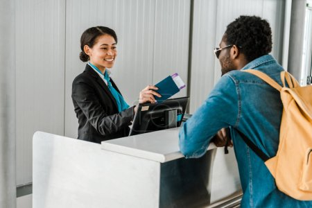 Photo pour Souriant travailleur afro-américain de l'aéroport donnant passeport et billet d'avion pour le touriste avec sac à dos - image libre de droit