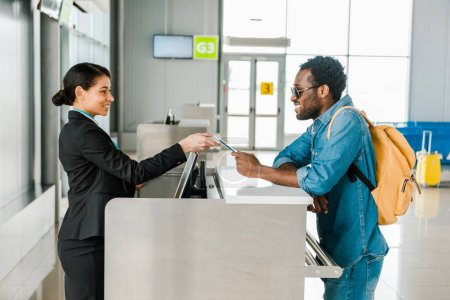 Photo pour Souriant travailleur de l'aéroport d'afro-américain prenant le passeport et le billet d'avion du touriste avec le sac à dos - image libre de droit
