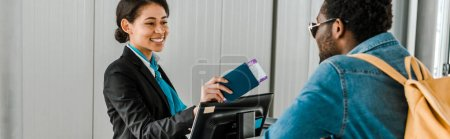 Photo for Panoramic shot of smiling african american airport worker giving passport and air ticket to tourist with backpack - Royalty Free Image