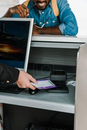 Photo pour Vue recadrée du billet d'avion de balayage de travailleur d'aéroport au contrôle de ticket dans l'aéroport - image libre de droit