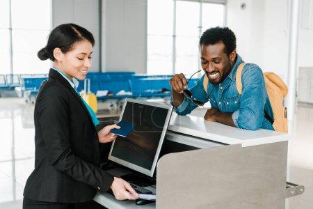 Photo pour Souriant travailleur afro-américain de l'aéroport de contrôle des billets d'avion et passeport au contrôle des billets à l'aéroport - image libre de droit