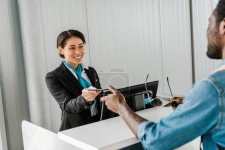 Photo pour Souriant afro-américain travailleur de l'aéroport donnant des documents au touriste - image libre de droit