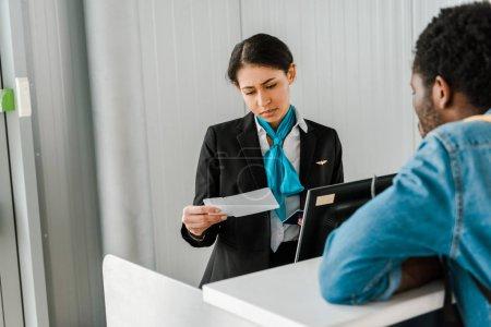 Photo pour Travailleur afro-américain concentré de l'aéroport à la recherche de billets d'avion - image libre de droit