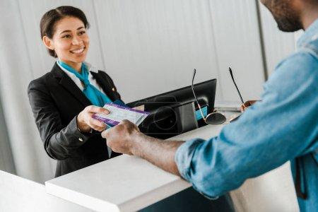 Photo pour Joyeux travailleur afro-américain de l'aéroport donnant passeport et billet d'avion au touriste - image libre de droit