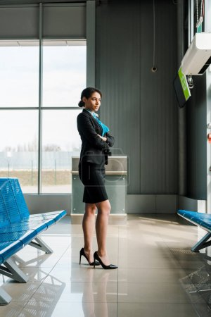 Photo for Beautiful african american stewardess standing with crossed arms in airport and looking away - Royalty Free Image