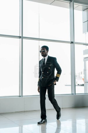 confident african american pilot in sunglasses walking in airport with hand in pocket