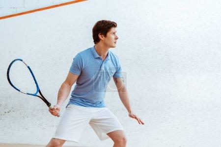 Photo pour Sportif concentré en polo bleu jouant au squash dans le centre sportif - image libre de droit