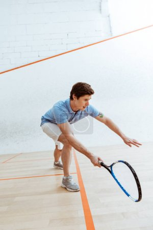 Photo pour Sportif émotif dans le polo bleu jouant le squash dans la cour à quatre murs - image libre de droit