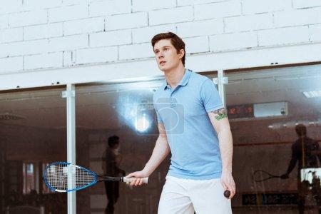 Photo pour Sportif dans le polo bleu jouant le squash dans la cour à quatre murs - image libre de droit