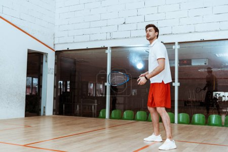 Photo for Full length view of sportsman in red shorts playing squash in four-walled court - Royalty Free Image