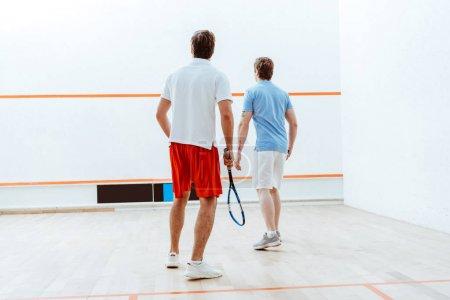 Foto de Vista trasera de dos deportistas jugando squash en cancha de cuatro paredes - Imagen libre de derechos