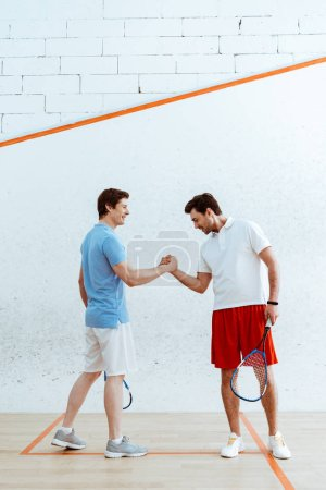 Foto de Two squash players with rackets shaking hands and looking at each other - Imagen libre de derechos
