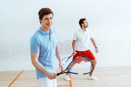 Foto de Guapo jugador de squash en polo azul mirando a la cámara - Imagen libre de derechos