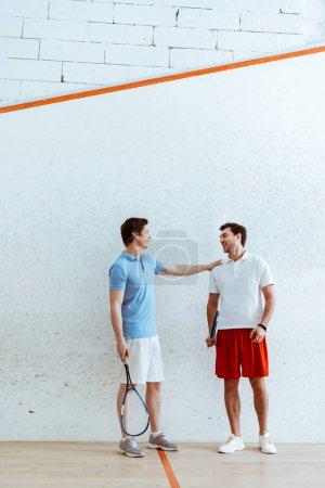 Photo pour Vue pleine longueur du joueur de squash mettant la main sur l'épaule de l'ami - image libre de droit