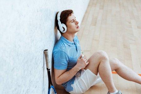 Joueur de squash assis sur le sol et écoutant de la musique les yeux fermés