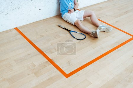 Foto de Cropped view of squash player sitting on floor and holding bottle of water - Imagen libre de derechos