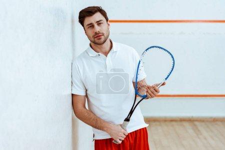 Photo pour Joueur barbu de courge retenant la raquette et regardant l'appareil-photo - image libre de droit