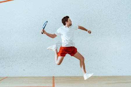 Photo for Sportsman in polo shirt jumping while playing squash in four-walled court - Royalty Free Image