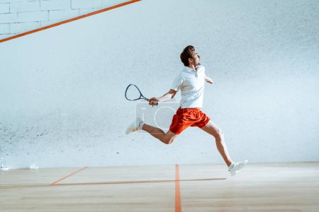 Photo for Full length view of sportsman with racket running while playing squash - Royalty Free Image