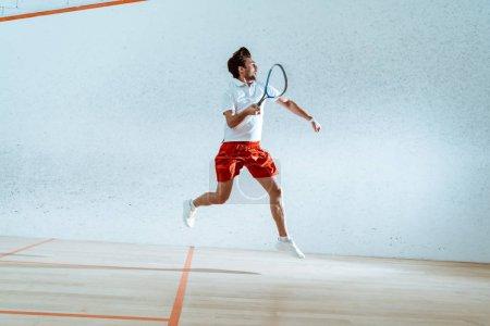 Photo pour Vue pleine longueur du sportif avec la course de raquette tout en jouant au squash - image libre de droit