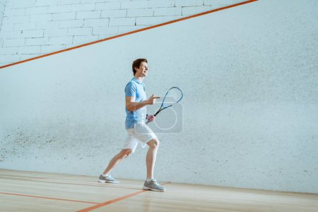 Full length view of smiling squash player pointing with finger