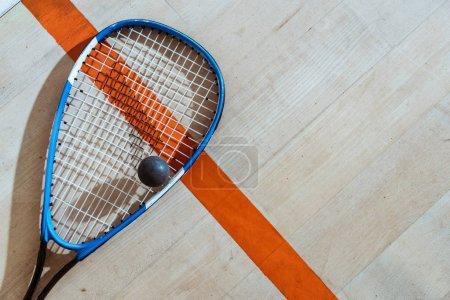 Photo pour Vue de dessus de raquette de squash et balle sur la surface en bois - image libre de droit